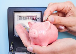 Female hands hold coin and pig piggy bank on a background of an electricity meter. Symbolic depiction of energy savings at home, utility bills, smart energy consumption