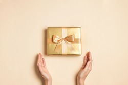 Female hands hold Golden gift with ribbon bow on beige background flat lay top view copy space. Holiday present, christmas, new year, birthday, valentine's day, 8 march. Surprise
