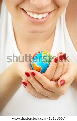 Female hands hold in hands with care a small copy of globe on a white background