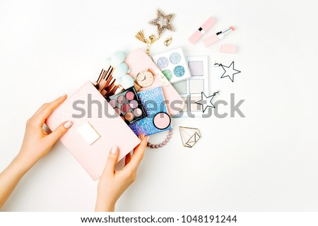 Female hands hold Makeup bag with cosmetic beauty products. Flat lay, top view. Beauty and Fashion concept