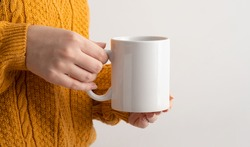 Female hands hold mock up white empty mug, cup for your design and logo close-up. Woman in yellow knitted sweater autumn winter. Blank template for promotional text message or promotional content