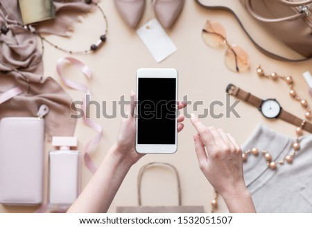 Female hands hold phone on fashion apparel background, girl customer shopper using online mobile shopping app choosing buying stylish trendy cloth with mobile payments on cell tech, close up top view