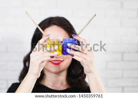 Female hands hold two paint jars and tassels in front of the face. Photo without a face. The concept of hobbies and hobbies. Photos in the interior.