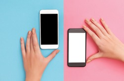 female hands hold two phones black and white