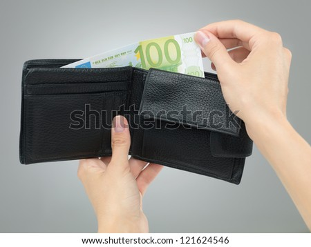 female hands holding a black leather wallet removing money from it on grey gradient background
