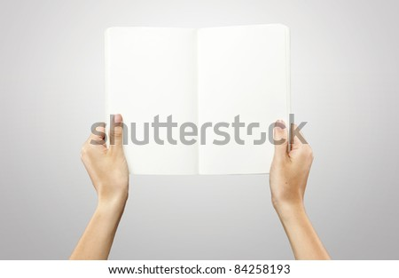 Female hands holding a blank white notebook. On a grey background