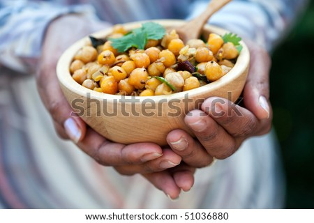 Female hands holding a bowl of chickpeas - stock photo