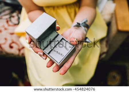 Female hands holding a box of silver earrings. The girl dressed in a yellow dress, her fingers manicure. Closeup.