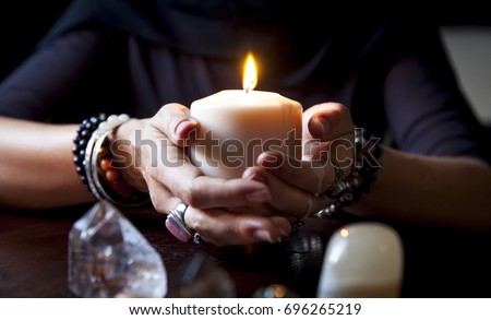 female hands holding a burning candle #696265219