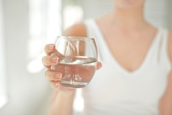 Female hands holding a clear glass of water. Slim body on background.