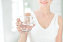 Female hands holding a clear glass of water. Slime body on background.