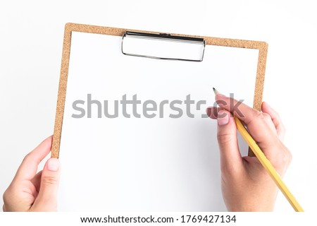 female hands holding a clipboard with a white sheet of paper on a white background. woman about to write a note on empty blank with a pencil, top view