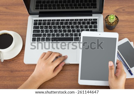female hands holding a computer tablet and laptop on the table in the office