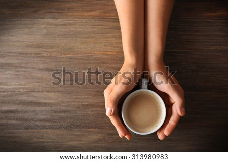 Female hands holding a cup of coffee with foam over wooden table, top view #313980983