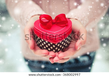 Female hands holding a gift box shaped of heart. The Valentines day and Christmas theme