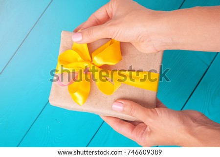 Female hands holding a gift. The girl unpacks the gift. The woman gives you a gift. Yellow bow on the gift. Rotated view with flash