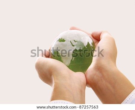 Female hands holding a glass globe isolated on white background