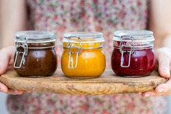 Female hands holding a home made vegan raw jams in a glass jar with spring colors. Healthy raw jam in a cup. Plum, apricot and raspberry jam on a wooden plate.