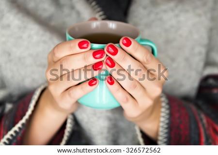 female hands holding a mug of hot tea