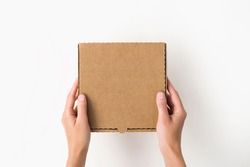 female hands holding a small cardboard box on a white background. packaging and delivery concept, top view