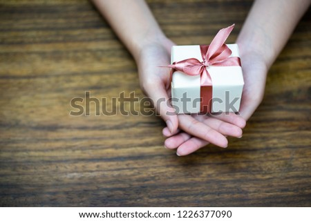 Female hands holding a small gift wrapped with pink ribbon on wood background. Selective focus,Selective focus,Valentines day #1226377090