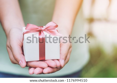 Female hands holding a small gift wrapped with pink ribbon. Selective focus,Selective focus,Valentines day #1176994510