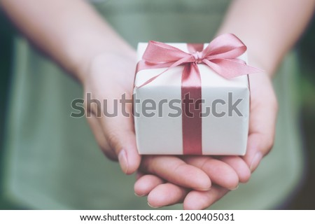 Female hands holding a small gift wrapped with pink ribbon. Selective focus,Selective focus,Valentines day #1200405031