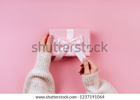 Female hands holding a small gift wrapped with pink ribbon. Selective focus,Selective focus #1237191064