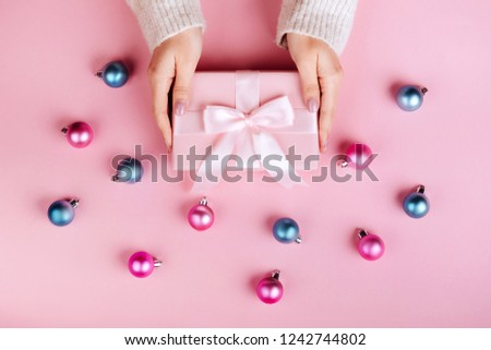 Female hands holding a small gift wrapped with pink ribbon. Selective focus,Selective focus #1242744802