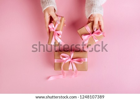 Female hands holding a small gift wrapped with pink ribbon. Selective focus,Selective focus #1248107389