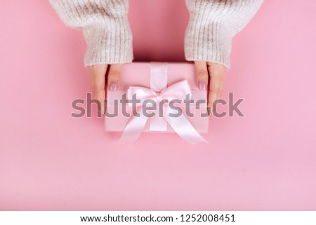 Female hands holding a small gift wrapped with pink ribbon. Selective focus,Selective focus #1252008451