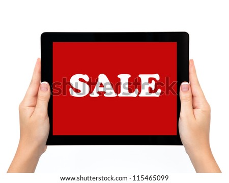 female hands holding a tablet touch computer pad gadget with the word sale on a red screen