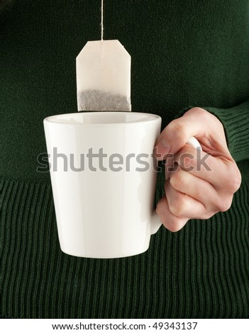 female hands holding a teacup and teabag, studio shot