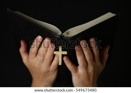 Shutterstock Female hands holding an open Bible with a crucifix.The concept of religion.