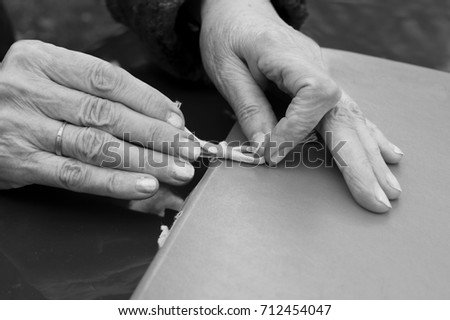 Female hands holding an orange retro looking folder, in black and white #712454047