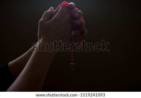 Female hands holding and hanging a red rosary on black background. Woman with Christian Catholic religious faith. Closeup image of hands and rosary. Holding rosary with white background