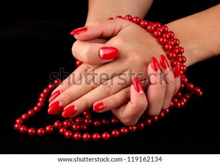 Female hands holding beads on color background