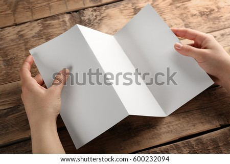 Female hands holding blank brochure on wooden background