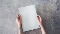Female hands holding blank white paper