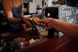 Female hands holding card against nfs payment machine to make payment for purchase in cafe