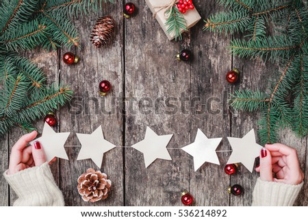 Female hands holding Christmas garland of stars on wooden background with Christmas gifts, Fir branches, red decorations. Xmas and Happy New Year composition. Flat lay, top view #536214892