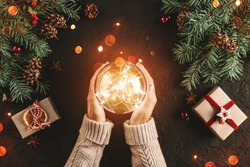Female hands holding Christmas glowing ball on holiday background with Fir branches, gifts. Xmas and Happy New Year card, bokeh, sparking. Flat lay, top view