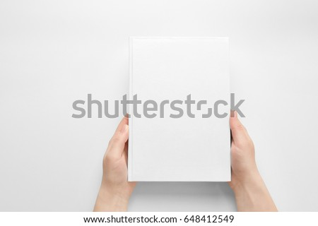 Female hands holding closed book with blank cover on light background #648412549