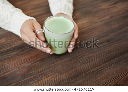 Female hands holding cup of green matcha tea on wooden background #471576119