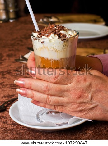 female hands holding cup of latte