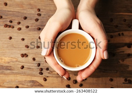 Female hands holding cup with coffee beans on wooden table background