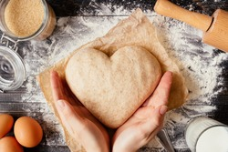 female hands holding dough in heart shape top view. Baking ingredients on the dark wooden table