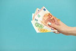 Female hands holding euro banknotes on a blue background. Euro Money. euro cash background
