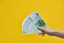Female hands holding euro banknotes on blue background. Euro Money Cash background