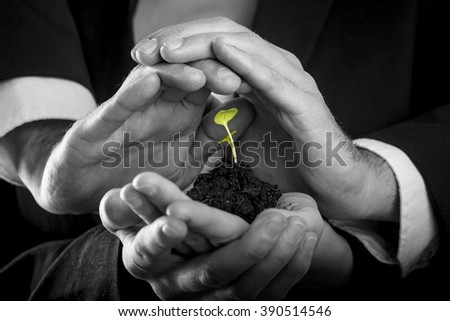 Female hands holding fertile soil from which a green sprout is growing and male hands making protective gesture above it. Conceptual of protection, teamwork and business start up.